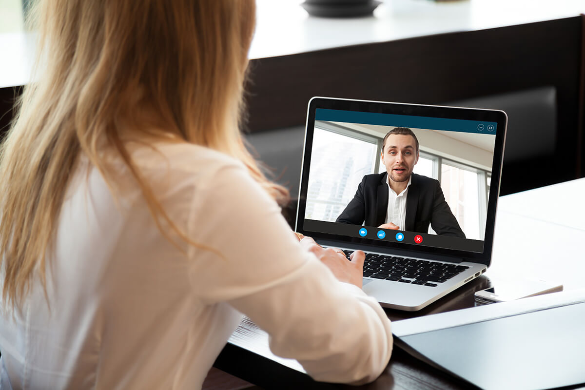 Business woman video conferencing with business man